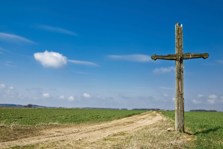 Old wooden cross at country road. Green grass and blue sky.